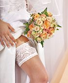 Garter at leg of bride and flower bouquet.