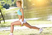 stock photo of boot camp  - fitness instructor exercising with small weights in green park - JPG