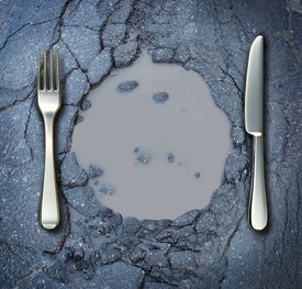 picture of water shortage  - Poverty and hunger concept with a fork and knife on a broken asphalt road shaped as a dinner plate as a social problem of food shortage hardships caused by financial distress or natural disaster resulting in living poor on the streets as a health risk - JPG