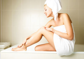 stock photo of body-lotion  - beautiful happy woman pampering herself and applying body lotion in the bathroom after the shower - JPG