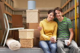 pic of moving van  - Portrait of smiling young couple sitting back of moving van - JPG