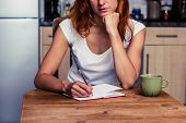 stock photo of anonymous  - Woman Makng A Shopping List In Her Kitchen