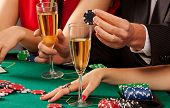 stock photo of gambler  - Gamblers holding casino chips and glasses of champagne - JPG