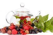 Teekanne mit Früchtetee und grüne Blätter