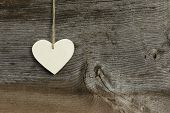 White Love Valentine's Heart Hanging On Wooden Texture Background