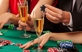 image of gambler  - Gamblers holding casino chips and glasses of champagne - JPG
