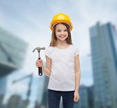 construction and people concept - smiling little girl in protective helmet with hammer