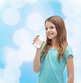 health and beauty concept - smiling little girl with glass of water
