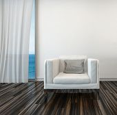 Armchair on a wooden parquet floor alongside a curtained window with a view of the sea in a living r