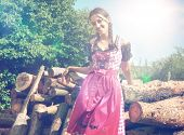 Bavarian girl in traditional dirndl posing outside in nature