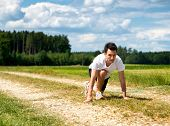 Handsome fit male runner in the ready position to sprint crouching down on a rural track in scenic c