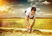 Athlete pausing on a rural track in green open countryside to tie his laces on a morning run as he d