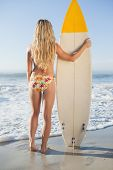 Gorgeous blonde surfer in bikini holding her board on a sunny day