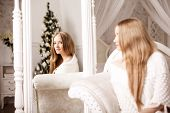 Beautiful young woman in white near the Christmas tree. Beautiful girl celebrates Christmas near the