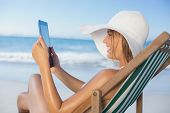 Smiling woman relaxing in deck chair on the beach using tablet on a sunny day