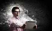 picture of mass media  - Young man looking shocked in tablet pc - JPG