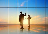 Silhouettes of businesspeople standing against panoramic office window