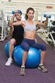 Trainer watching client lift dumbbells on exercise ball at the gym