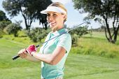 Female golfer smiling at camera on a sunny day at the golf course