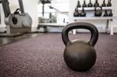 Black kettlebell on the weights room floor at the gym