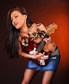 Aggressive young woman with tattoo playing guitar.