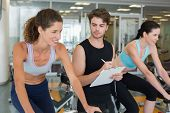 Fit women in a spin class with trainer taking notes at the gym