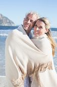 Happy couple wrapped up in blanket on the beach on a sunny day