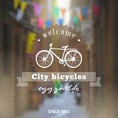 Vintage design touristic lettering with bicycle silhouette on the old european street defocused background