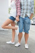 Couple in check shirts and denim holding hands on a sunny day in the city