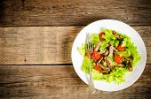 Green Salad With Tomatoes And Roast Beef In A White Dish