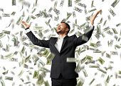 foto of excite  - happy excited businessman raising hands up and looking up under money rain - JPG