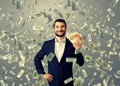 happy smiley businessman standing under money rain and holding euro
