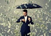young businessman with black umbrella standing under money rain and looking at watch