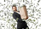 young businessman holding heavy paper bag with money under dollar's rain