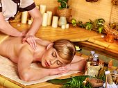 Woman getting stone massage in  spa near water.
