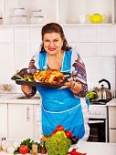 Mature woman preparing chicken dinner at kitchen.