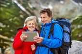 Senior hikers couple with tablet