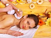 Woman getting herbal ball massage  in spa.