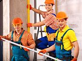 Happy group men in builder uniform indoor.