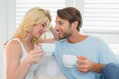 Smiling casual couple sitting on couch having coffee at home in the living room