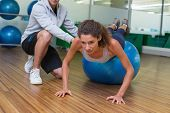 Trainer helping his client doing push up on exercise ball at the gym