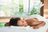 Gorgeous woman lying on massage table with salt treatment on back at the health spa