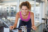 Pretty fit woman on the bike smiling at camera at the gym
