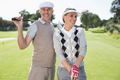 Golfing couple smiling and holding clubs on a sunny day at the golf course