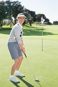 stock photo of ladies golf  - Lady golfer on the putting green at the eighteenth hole smiling at camera on a sunny day at the golf course - JPG