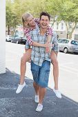 Young hip man giving his blonde girlfriend a piggy back on a sunny day in the city