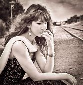 Beautiful young girl thoughtfully sitting on a train station. Sepia.