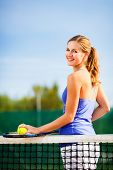 Portrait of a pretty, young tennis player  on  a court on a lovely summer day