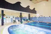 MOSCOW, RUSSIA - MAY 8, 2014: Indoor pool of fitness center Gold Gym with traineger equipments. In R