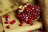 Raw red bright pomegranate with seeds on sacking background